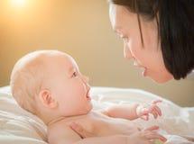 Mischrasse chinesisch und kaukasisches Baby, das in Bett mit seinem legt lizenzfreies stockbild
