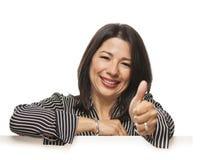 Mischrasse-Frau, die auf leerem weißem Zeichen mit den Daumen oben sich lehnt Stockbilder