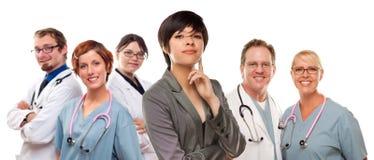 Mischrasse-Frau mit Doktoren und Krankenschwestern hinten Lizenzfreie Stockfotos