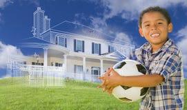 Mischrasse-Junge, der Ball mit Ghosted-Haus-Zeichnung hinten hält Stockbilder