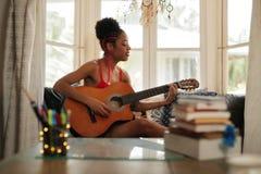 Mischrasse-Mädchen, das zu Hause klassische Gitarre singt und spielt Lizenzfreies Stockfoto