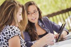Mischrasse-Mädchen, die zusammen an Tablet-Computer arbeiten Lizenzfreie Stockfotos
