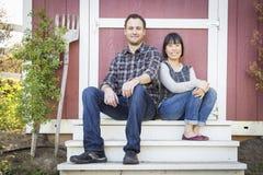 Mischrasse-Paare, die auf den Schritten sich entspannen Lizenzfreie Stockfotos