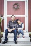 Mischrasse-Paare, die auf den Schritten sich entspannen Stockfoto