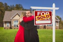 Mischrasse-Paare umarmend, verkaufte Haus, Real Estate-Zeichen Lizenzfreies Stockbild