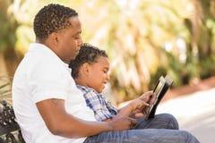 Mischrasse-Vater und Sohn, der Noten-Auflage-Computer-Tablette verwendet Stockfotos