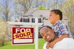 Mischrasse-Vater und Sohn vor Real Estate-Zeichen und -haus Lizenzfreie Stockfotos