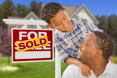 Mischrasse-Vater und Sohn vor Real Estate-Zeichen und -haus Lizenzfreie Stockbilder