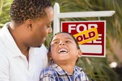 Mischrasse-Vater und Sohn vor Verkaufs-Real Estate-Zeichen Lizenzfreie Stockfotografie
