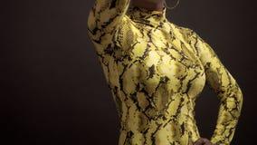 Mischrasseafroamerikanerfrau im hellen gelben Kleid mit Pythonschlangendruck 90 ` s Art stock footage
