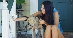 Mischrassefrau, die auf dem Portal macht Fotos mit Hund sitzt Stockbild