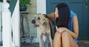 Mischrassefrau, die auf dem Portal macht Fotos mit Hund sitzt Lizenzfreies Stockbild