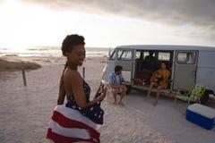 Mischrassefrau, die eine amerikanische Flagge gegen seine Freunde im Hintergrund hält stockbild