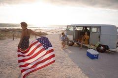Mischrassefrau, die eine amerikanische Flagge gegen seine Freunde im Hintergrund h?lt stockbilder