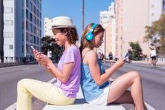 MischrasseFreundinnen zurück zu Rückseite hörend Musik in der Straße ohne Verkehr Konzept der Technologie, Social Media, stockbilder