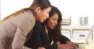 Mischrassegeschäftskollegen, die am Schreibtisch mit Laptop arbeiten Lizenzfreie Stockbilder