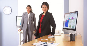 Mischrassegeschäftskollegen, die am Schreibtisch mit Laptop arbeiten Lizenzfreies Stockbild