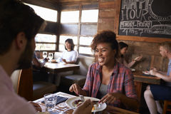 Mischrassepaare, die im beschäftigten Restaurant, Abschluss oben zu Mittag essen Lizenzfreie Stockfotos