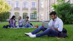 Mischrassestudent, der den Laptop, auf dem Campus sitzend auf Gras, Bildung online verwendet lizenzfreie stockbilder
