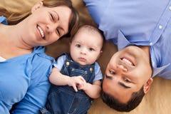 Mischrennen-Familie, die auf einer Decke liegt Lizenzfreies Stockfoto