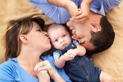 Mischrennen-Familie, die auf einer Decke Snuggling ist Stockfotos