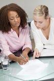 Mischrennen-junge Geschäftsfrauen, die einen Vertrag unterzeichnen Stockbilder
