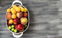Mischsommerfruchtbilder in einem Korb, weißer Hintergrund mit einem Korb von Pfirsichen, Pflaumen, Äpfel, Nektarinen, Aprikosenbi Lizenzfreie Stockfotos