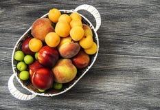 Mischsommerfruchtbilder in einem Korb, weißer Hintergrund mit einem Korb von Pfirsichen, Pflaumen, Äpfel, Nektarinen, Aprikosenbi Stockfotografie