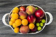 Mischsommerfruchtbilder in einem Korb, weißer Hintergrund mit einem Korb von Pfirsichen, Pflaumen, Äpfel, Nektarinen, Aprikosenbi Stockfoto
