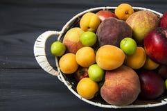 Mischsommerfruchtbilder in einem Korb, weißer Hintergrund mit einem Korb von Pfirsichen, Pflaumen, Äpfel, Nektarinen, Aprikosenbi Lizenzfreie Stockfotografie