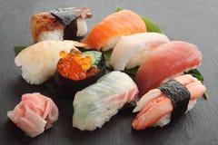 Mischsushi-Servierplatte auf schwarzer Steinplatte, japanisches Lebensmittel Lizenzfreie Stockbilder
