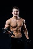 Mischt das athletische Manntraining der hübschen Energie, das oben pumpt, mit Dummköpfen in einer Turnhalle mit Muskulöser Körper Stockfotografie