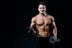 Mischt das athletische Manntraining der hübschen Energie, das oben pumpt, mit Dummköpfen in einer Turnhalle mit Muskulöser Körper Stockfoto