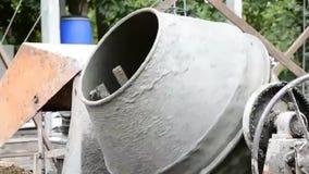 Mischtrommelmaschine und -arbeiter, die im Konstruktstandort arbeiten stock footage