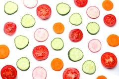 Mischung der geschnittenen Gurke mit geschnittener Karotte und der Tomate lokalisiert auf einer Draufsicht des weißen Hintergrund stockfotografie