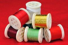Mischung des farbigen Threads auf einem roten Hintergrund Lizenzfreie Stockfotos