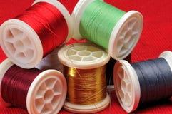 Mischung des farbigen Threads auf einem roten Hintergrund Lizenzfreie Stockfotografie