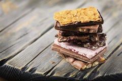 Mischung des süßen Schweizer choccolate auf dem Holztisch Lizenzfreie Stockfotos