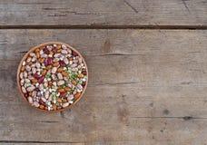 Mischung von Bohnenvielzahl, von azuki und von grünen Linsen in einer Schüssel auf einer verwitterten hölzernen Planke Nahrungsmi stockbilder