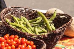 Mischung von bunten Kirschtomaten und -Stangenbohnen in den Körben Stockfoto