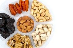 Mischung von Früchten und von Nüssen auf einem Behälter lokalisiert auf Weiß Stockfotos
