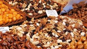 Mischung von Gestellen mit Daten trocknen Fruchtrosinen und -nüsse im Markt La Boqueria in Barcelona, Spanien stock footage