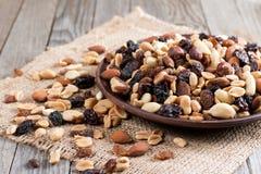 Mischung von Nüssen und von Trockenfrüchten in einer Schüssel auf einem hölzernen Hintergrund Gesunde Nahrung Lizenzfreie Stockbilder