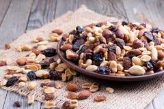 Mischung von Nüssen und von Trockenfrüchten in einer Schüssel auf einem hölzernen Hintergrund Gesunde Nahrung Lizenzfreies Stockfoto
