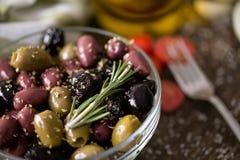 Mischung von Oliven im Öl mit Gewürzen Stockfoto