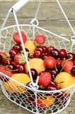 Mischung von Sommerfrüchten und -beeren im Drahtkorb Stockfoto