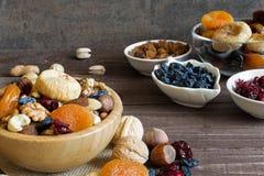 Mischung von Trockenfrüchten und von Nüssen in einer Schüssel auf rustikalem hölzernem Hintergrund Stockfotos
