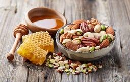Mischungsnüsse mit Bienenwaben und Honig Stockbild