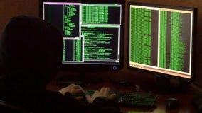 Misdadige hakker met het zwarte systeem van het kap doordringende netwerk van zijn donkere hakkerruimte stock video