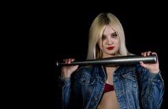 Misdadige jonge vrouw met honkbalknuppel, jonge hooligan in jeans en een denimjasje stock afbeeldingen
